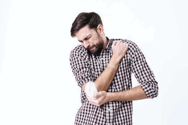 De arm van een man doet pijn. zijn gezicht grijnst van de pijn.