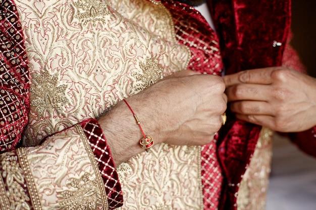 De armen van de bruidegom met rode armband knoop omhoog gouden huwelijkskostuum