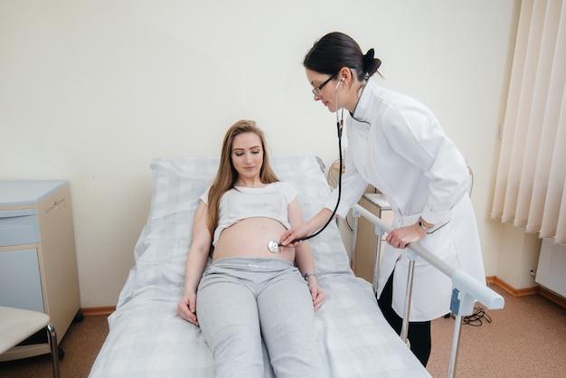 De arts adviseert en bedient een jong zwanger meisje in een medische kliniek. geneeskundig onderzoek