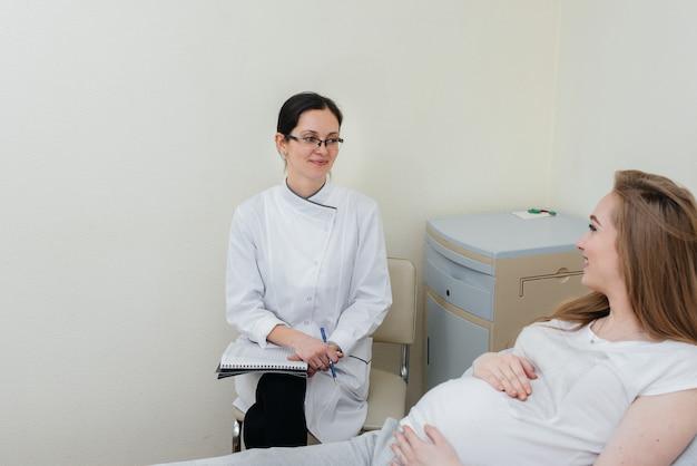 De arts adviseert en bedient een jong zwanger meisje in een medische kliniek. geneeskundig onderzoek.