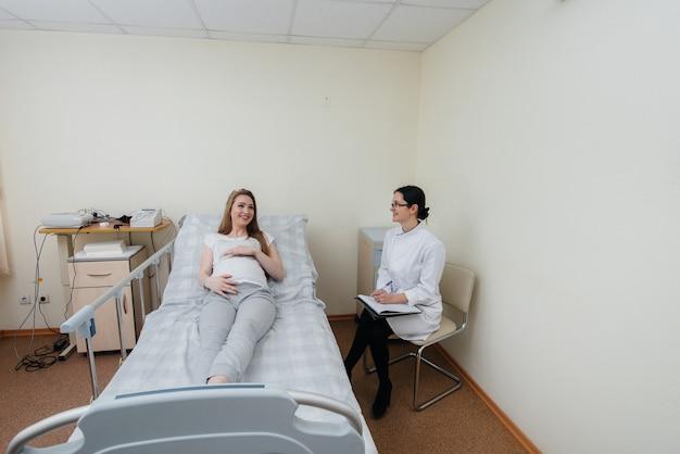 De arts adviseert en bedient een jong zwanger meisje in een medische kliniek.