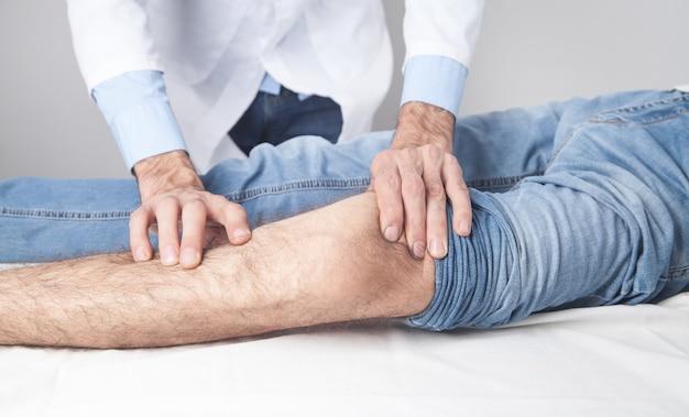 De arts behandelt de knie aan de patiënt