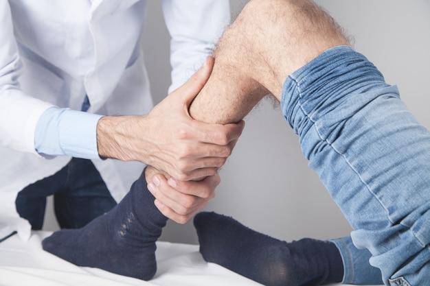 De arts behandelt de knie aan de patiënt.