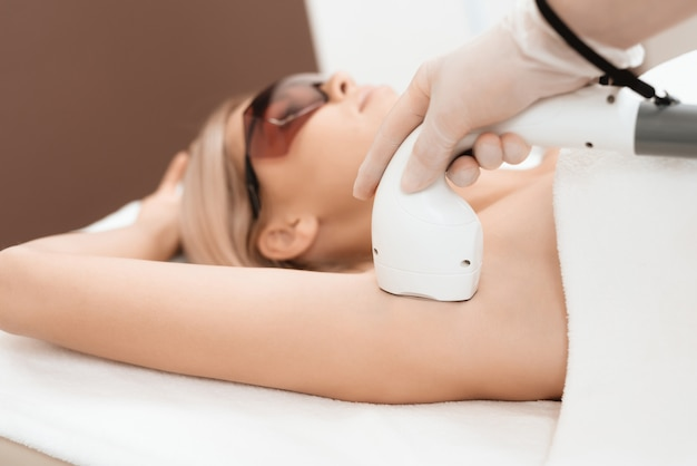 De arts behandelt haar oksels met een apparaat