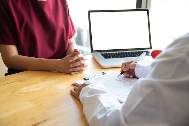 De arts bespreekt met de patiënt na een lichamelijk onderzoek van de resultaten en behandelingsrichtlijnen.