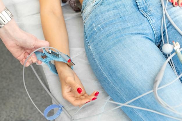 De arts bevestigt de elektroden van de ecg-pegs aan de pols van de patiënt