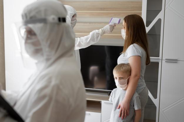 De arts controleert de lichaamstemperatuur van de patiënt met behulp van een infrarood voorhoofdthermopistool