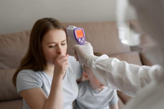 De arts controleert de lichaamstemperatuur van de patiënt thuis met behulp van een infrarood voorhoofdthermometer. coronavirus, covid-19, hoge koorts en hoest