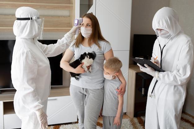 De arts controleert de lichaamstemperatuur van de patiënt thuis met behulp van een infrarood voorhoofdthermometer. coronavirus, covid-19, quarantaine, hoge temperatuur.