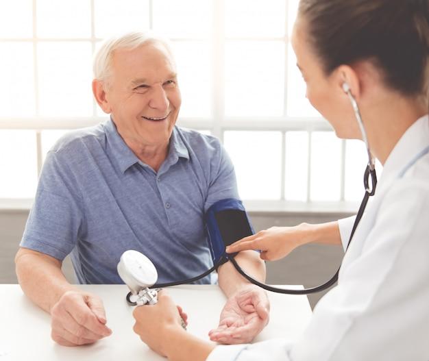 De arts controleert de pols van een oude patiënt in de kliniek