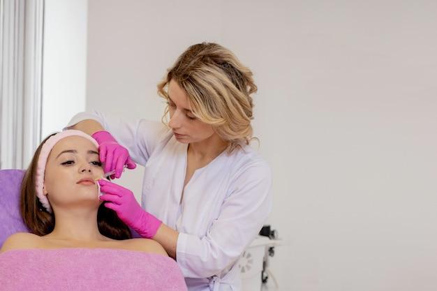 De arts-cosmetoloog maakt de procedure voor verjongende gezichtsinjecties voor aanscherping