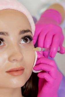 De arts-cosmetoloog maakt de procedure voor verjongende gezichtsinjecties voor het aanscherpen en gladstrijken van rimpels op de gezichtshuid van een mooie, jonge vrouw in een schoonheidssalon.