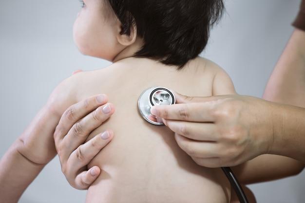 De arts die aziatisch babymeisje onderzoekt en luistert haar hart slaat met stethoscoop in het ziekenhuis