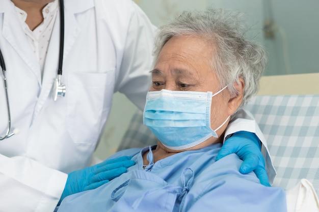 De arts die aziatische hogere vrouwenpatiënt controleren die een gezichtsmasker in het ziekenhuis dragen beschermt covid-19 virus.