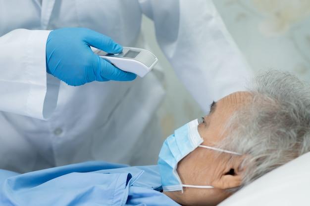 De arts die digitale thermometer houdt om aziatische hogere vrouwenpatiënt te meten voor beschermt covid-19 virus.