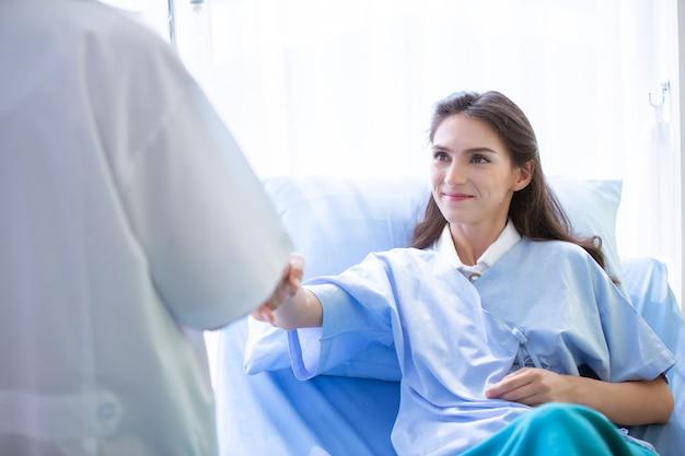 De arts die handen vasthoudt om de patiënt bij het bed op te vrolijken