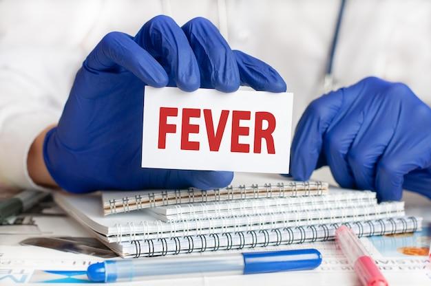 De arts dient blauwe handschoenen in met een kaart met de tekst fever op houten tafel met een stethoscoop en kladblok voor medische dossiers. medisch en gezondheidszorgconcept. selectieve aandacht