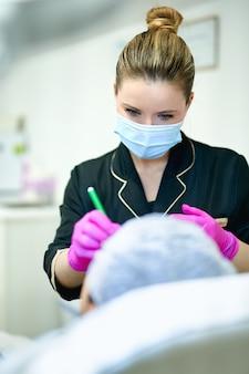 De arts dient handschoen in die tekens op het gezicht van de patiënt maakt