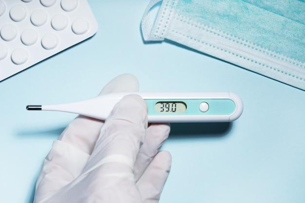 De arts dient handschoenen in die de temperatuur van de patiënt meten 39. coronavirus covid-19 pandemische behandeling, preventie, bescherming uitbraakconcept.