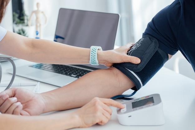 De arts draagt een manometer waarmee de patiënt de druk kan controleren.