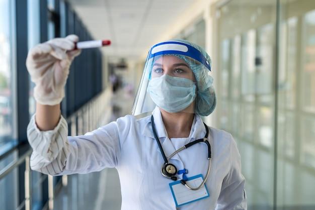 De arts draagt een uniform gezichtsmasker en een schild dat de reageerbuis op het bloed van de patiënt houdt. covid-19 quarantaineconcept