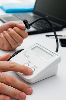 De arts drukt op de tonometer-knop. meting van bloeddruk in het kantoor van de arts. artsenoverleg in een kliniek of ziekenhuis