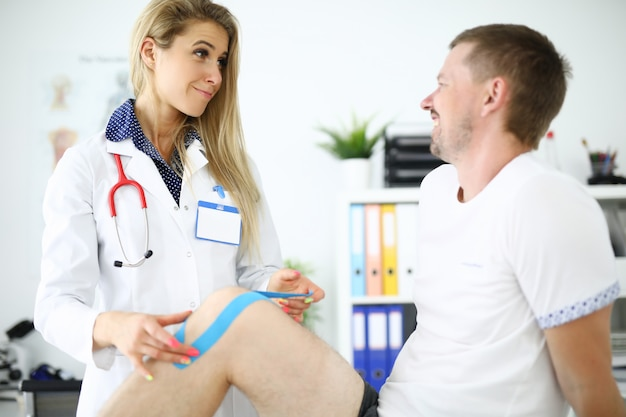 De arts en de patiënt glimlachen en bevestigen kinesioband op been