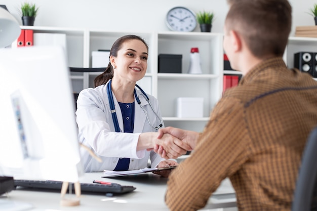 De arts en de patiënt schudden elkaar de hand.