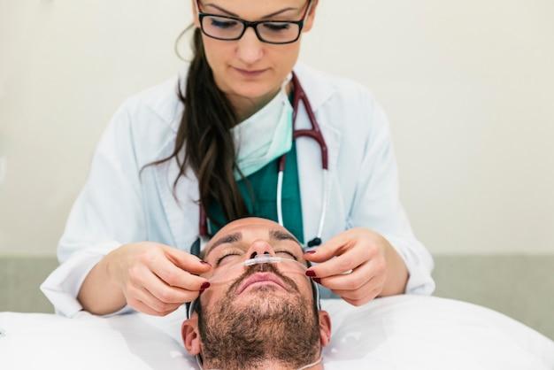 De arts geeft een zieke patiënt.