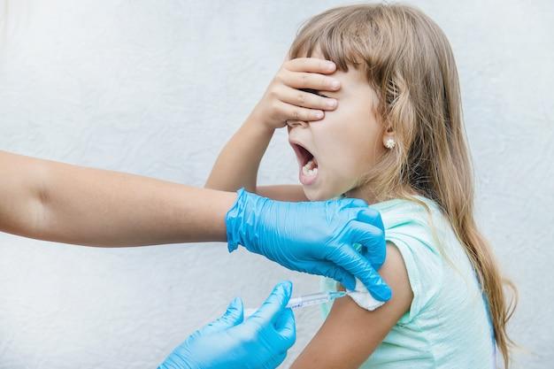 De arts geeft het kind een injectie in de arm