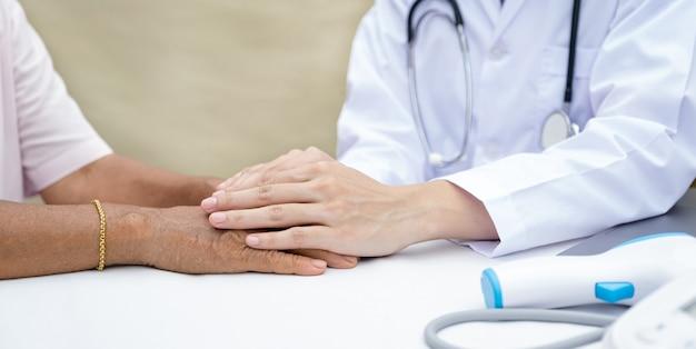 De arts hand in hand om de resultaten van het gezondheidsonderzoek aan te moedigen en uit te leggen aan de oudere patiënt