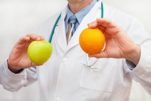 De arts heeft een appel en een sinaasappel voor een gezond dieet