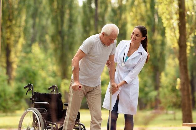 De arts helpt de oude man op krukken te staan.