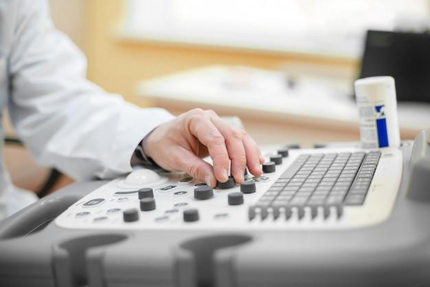 De arts houdt een echografie op de patiënt, een hand dicht omhoog