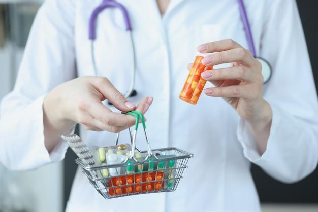 De arts houdt een mandje met pillen in zijn hand. apotheekproducten voor gezondheidsconcept