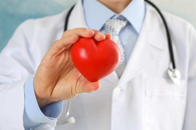 De arts houdt hart tegen blauwe oppervlakte, omhoog sluit