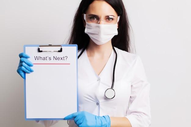 De arts in een handschoenen, masker en glazen houdt blad met tekst wat nu.