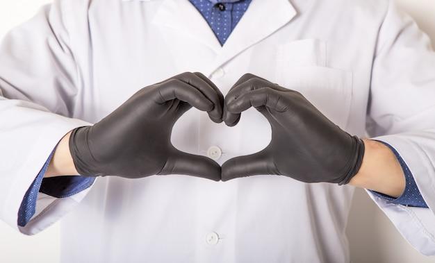 De arts in medische handschoenen, toont hartsymbool met hand