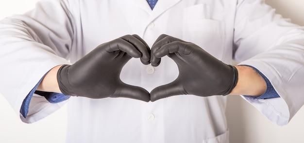 De arts in medische handschoenen, toont hartsymbool met handen