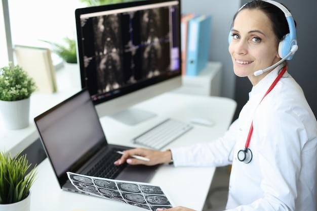 De arts is op de computer die een koptelefoon draagt en een röntgenfoto vasthoudt