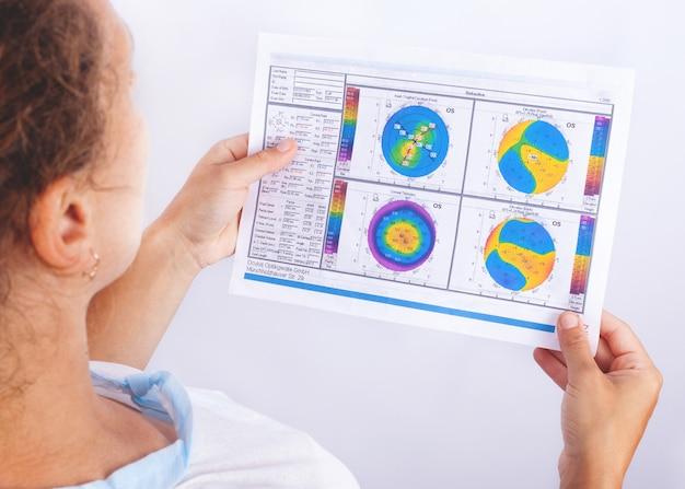 De arts kijkt naar de topografie van een patiënt wiens keratoconus 2-3 fasen. problemen met zien