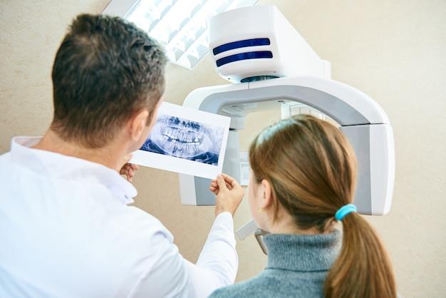De arts laat de patiënt een röntgenfoto zien