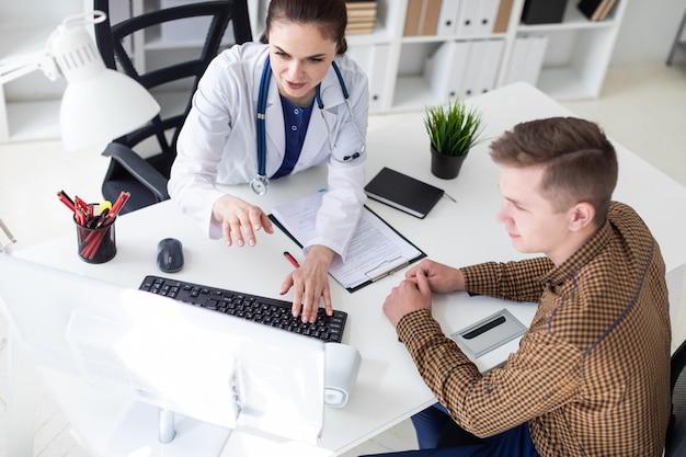 De arts legt het probleem aan de patiënt op de computer uit.