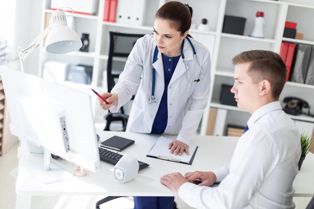 De arts legt het probleem uit aan de patiënt op de computer.