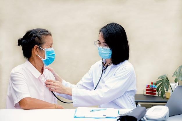 De arts luisterde met een stethoscoop naar de hartslag van de oudere patiënt.
