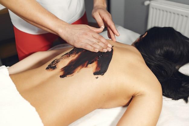 De arts masseert de vrouw met een chocolade