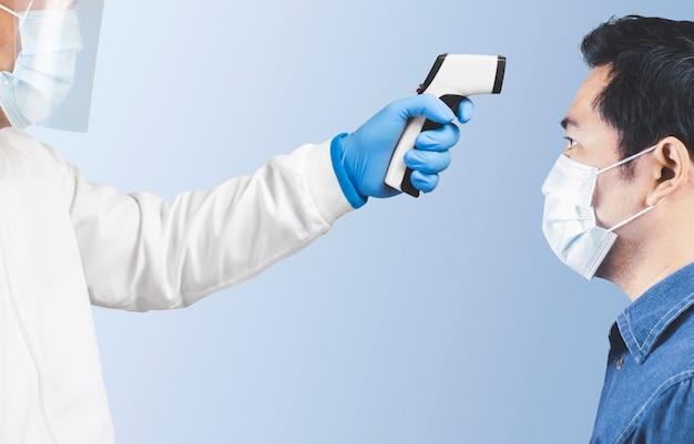 De arts meet de temperatuur van de patiënt met een infraroodthermometer
