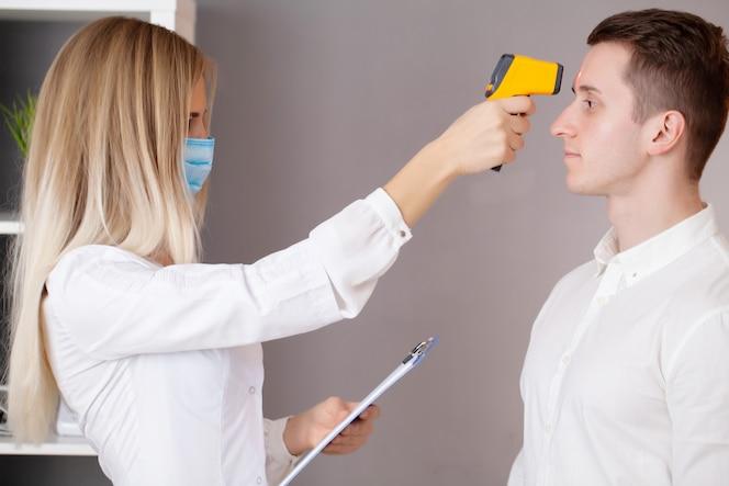 De arts meet de temperatuur van de patiënt met een laserthermometer