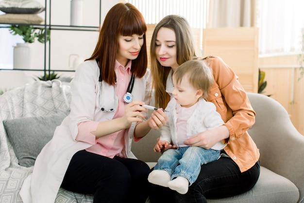 De arts meet en toont de temperatuur van het kleine meisje aan haar moeder. gezondheidszorg en geneeskunde concept op kinderarts afdeling.
