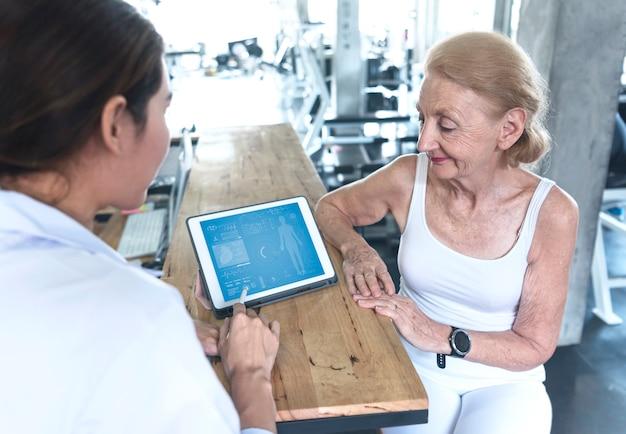 De arts met hogere vrouw in revalidatiecentrum controleert gezondheidszorg en toont gegevens iets op tablet.